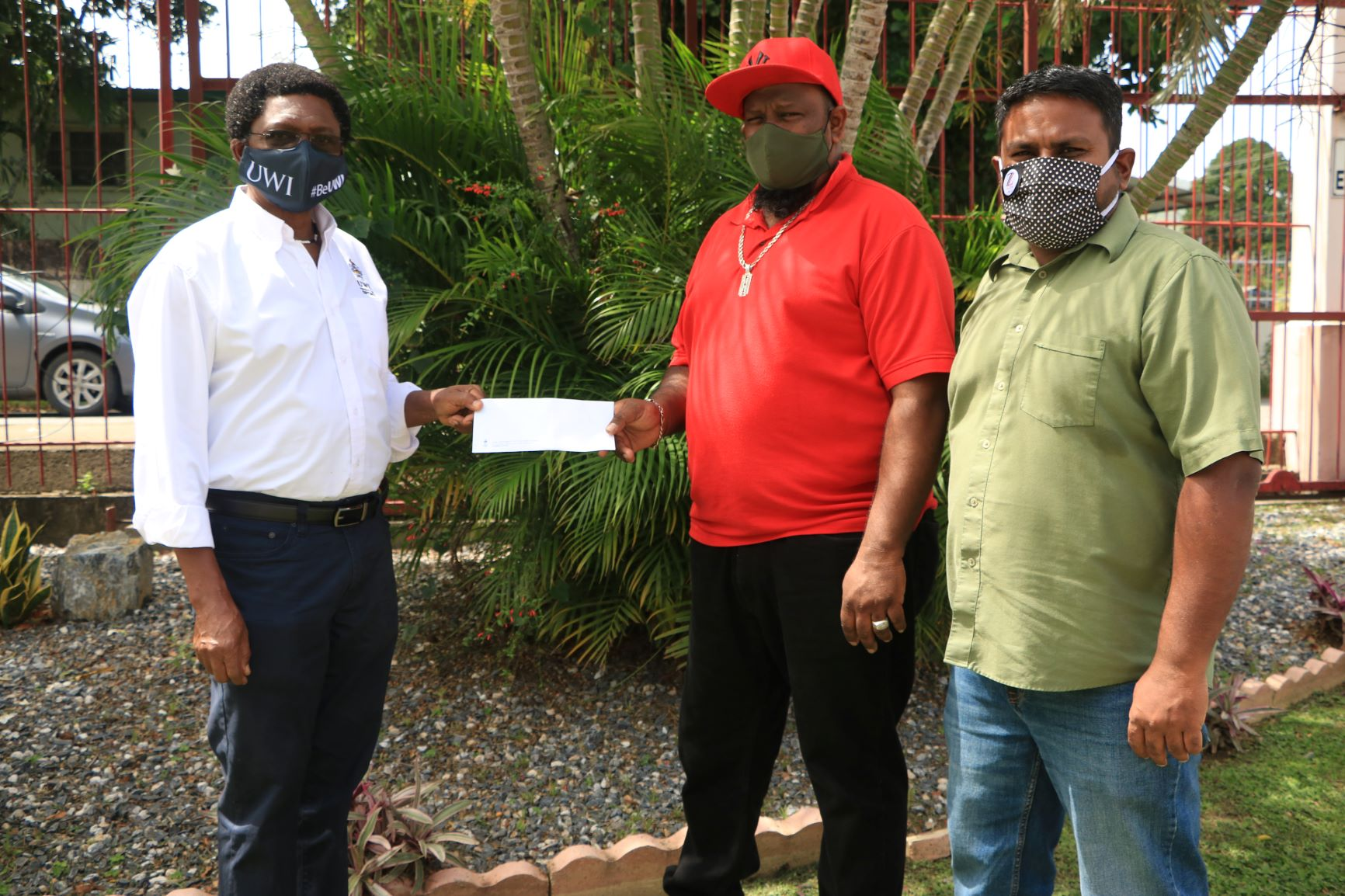 Head of the Academy of Sport, The UWI, Professor Funso Aiyejina presents a grant to Aaron Ramraj, father of CIP participant Ishmeel Ramraj, who is accompanied by Programme Coordinator, Community Inclusion Programme (CIP), Trinidad, Ryerson Bhagoo at The UWI SPEC
